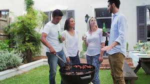 diverse group of friends cooking meat on fire and drinking beers having fun together at garden party lifestyle weekend