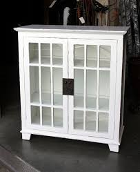 furniture square white wooden bookcase with double glass door having short base on ceramics flooring