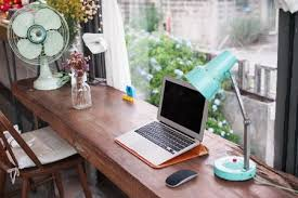 laptop and lamp by window on table
