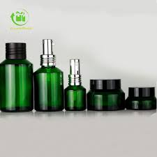 green glass bottles and jars set for skincare