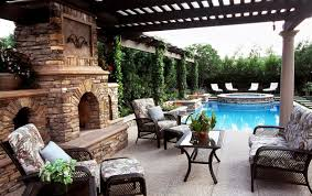 outdoor patio spaces stone flooring antique wicker chairs and table beside stone outdoor fireplace using t