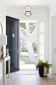 robert abbey mary mcdonald pythagoras pendant elegantly on display in the entrance hall of an entry foyer pleted with a black front door a modern nickel