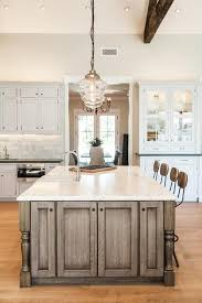 brown kitchen island and clear glass schoolhouse pendants