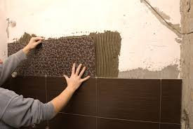 person installing brown patterned wall tile