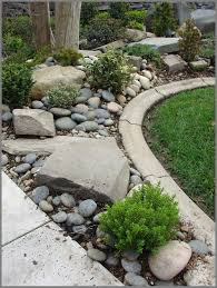 junipers holly boxwood and boxleaf euonymous give this river rock beach pebble and boulder rock garden a rugged and sy design feel diy garden rocks