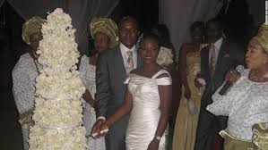 a nigerian couple cut their wedding cake surrounded by guests in traditional attire