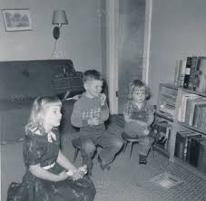 black kids watching tv. black and white photo of three children (two girls one boy) watching tv in early 1950s. oldest girl is dress, sitting on floor holding doll. kids tv