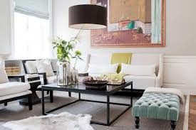 drum pendant lighting with black shade hung over a living room with modern furniture