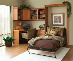 brown wooden murphy bed with dark brown bedding set on white rug completed by curved desk on the corner