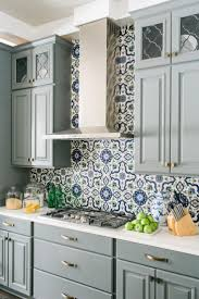 kitchen design entertaining includes:  blue and white tiled backsplash and floor to ceiling cabinets combined with a grandiose island for entertaining anchors this family friendly kitchen