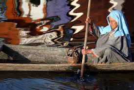 blind woman rowing a shikara in dal lake srinagar kashmir