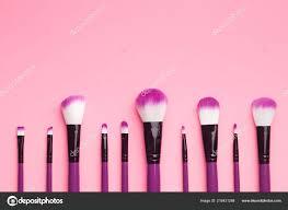 set makeup brushes pink background flat lay stock photo