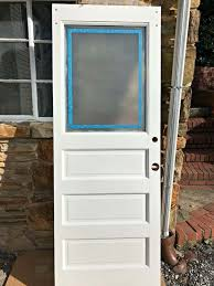 old white door with window taped with painter s tape and frosted