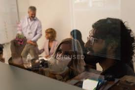 executives writing on glass wall in office stock photo