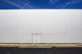 corrugated sheet metal wall with a door the street shadows and blue sky outdoor industrial look digital background for photographers stock image