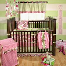 fresh colorful bedding pink patterned bedding stripped accent wall natural finished wood flooring dark finished crib pink polkadots accecories