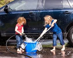 children use water hose nozzle for washing car