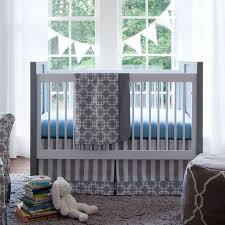 white gray wooden crib with blue bedding combined with gray white stripped and square pattern placed
