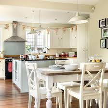 Family Kitchen With Off White Walls, Wood Flooring, White Dining Set And  Pendant