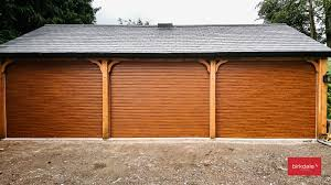roller garage doors with a golden oak laminated finish fitted to a triple garage