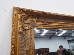 large rectangular bevelled edge wall mirror in ornate swept gilt frame with shell and leaf decoration