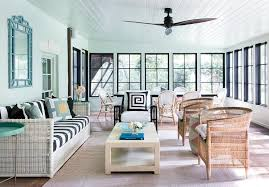 large sunroom with white wicker sofa with black and white striped cushions