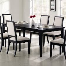 dining room table mirror top: stunning black rectangular dining table have coffee glass and flower vase on top with six dining chairs white cushions beside white painted wall decoration