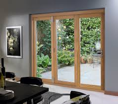 triple glass sliding doors with natural brown wooden frame combined with silver steel handler placed on the gray wall