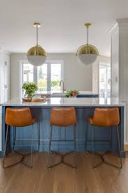 cb2 globe pendant lights hang over a blue kitchen island topped with a white quartz countertop seating three orange leather bar stools