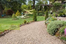 gravel path leading to raised beds with seating area under wooden pergola overlooking lawn and