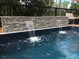 poolside faux stone waterfall built with norwich stacked stone panels in gray rock color
