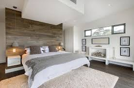 large bedroom with big white bed and gray wooden wall panel also white wall and ceiling