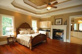 traditional bedroom ideas with color. An Elegant Master Bedroom With Rich Red Hardwood Floors, A Dual-sided Fireplace Shared Traditional Ideas Color