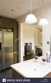 peninsula lighting. Pendant Lights Above Peninsula Unit With Glasses Of Red Wine In Modern Kitchen - Stock Image Lighting
