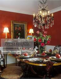 dining room white wainscoting red walls chandelier sideboard with lamps fl painting sits on top of sideboard tea set gerbera and rose fl