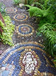 simple bands of colored pebbles in round stepping stones match the mosaic path of a rattle snake between my two houses the smaller rounds were made in the