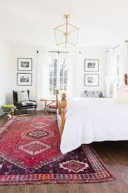 white bedroom with red area rug