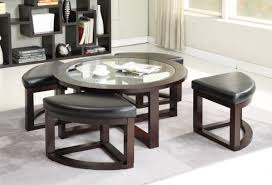 wooden table and case with white upholostered ottomans underneath on cream carpet as well as round glass coffee