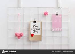 happy valentine s day card on a metal grid display with knitted pink heart and pom pom valentine s day decoration wall grid organizer photo by melica