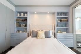 Ivory Wingback Tufted Headboard Flanked by Gray Built In Shelves and Drawers