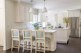 kitchen peninsula with blue leather counter stools and white pleated pendants