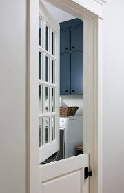 a white dutch door fitted with glass panels and an oil rubbed bronze door knob opens to a white and blue laundry room boasting stacked blue flat front
