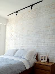 lighting in bedroom. brick finish not entirely white some color variation showing through also the black track light lighting in bedroom n