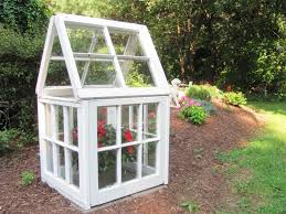 a small greenhouse made out windows in a backyard