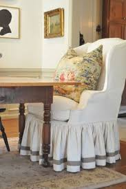 love wingback chair cover and love pillow now this is how i envision a dining room table two fy wingback chairs at either end and a mix of others on