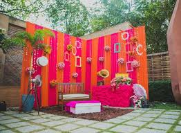 a fun and colouful wedding photo booth set up outdoors with a faux framed wall