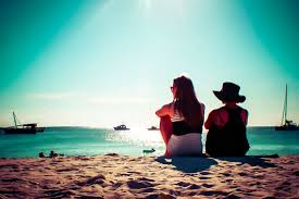 picture of mother and daughter sitting in the sand overlooking the sea and ships