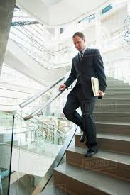 Office Stairs Man Walking Down Stairs In Office Stock Photo Dissolve