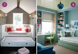 A trundle bed in the attic with pink throw pillows, and a blue and green