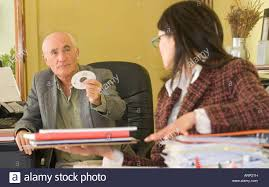 busy young w in office working her annoying boss older stock photo busy young w in office working her annoying boss older male colleague who is handing her a cd